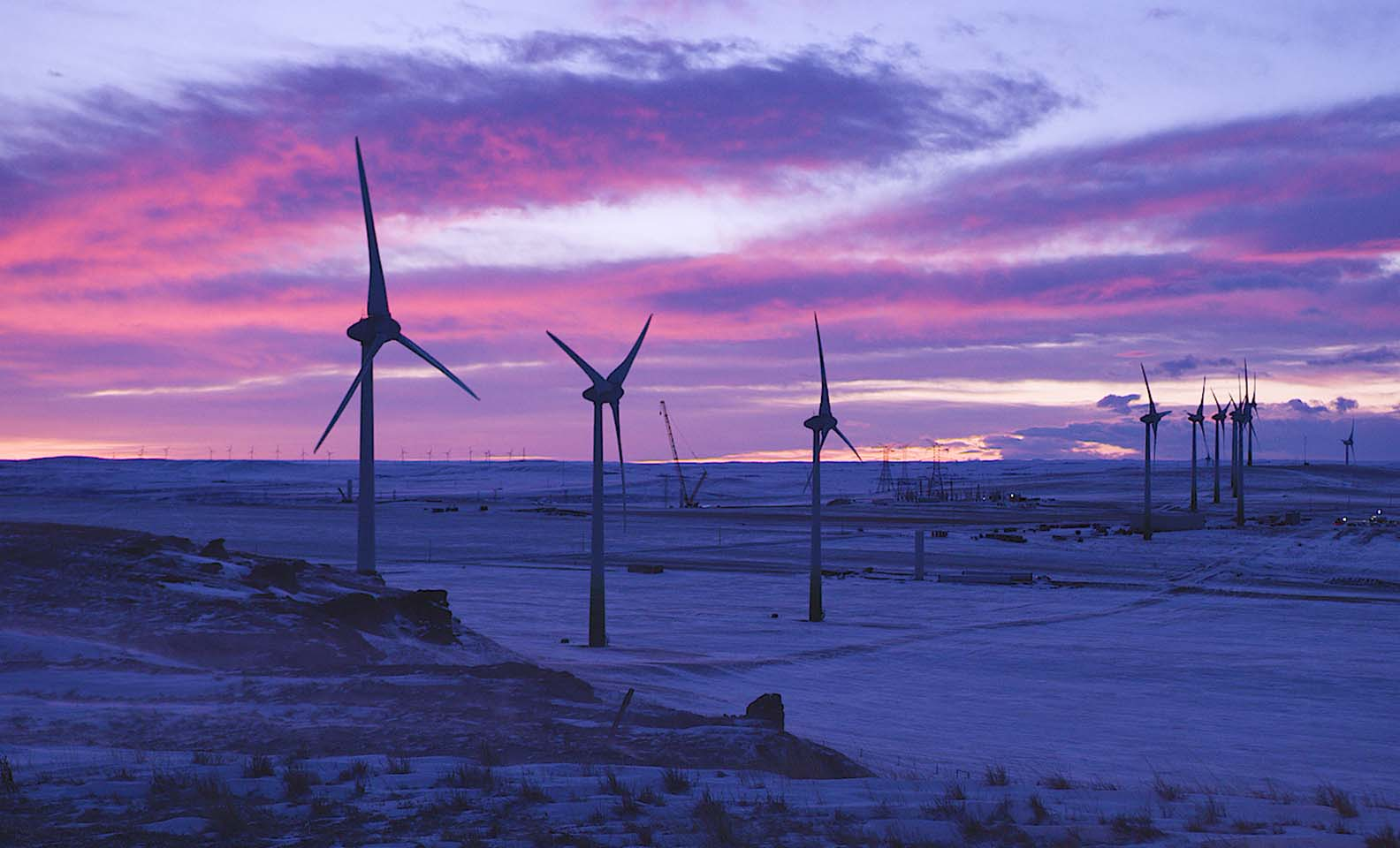 Wind turbines at sunset over snowy landscape